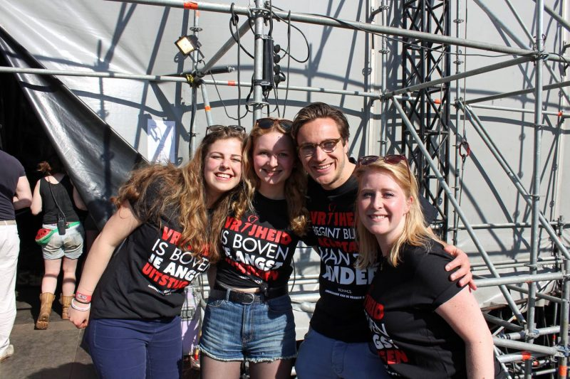 Vier BFU vrijwilligers poseren vrolijk backstage naast het podium