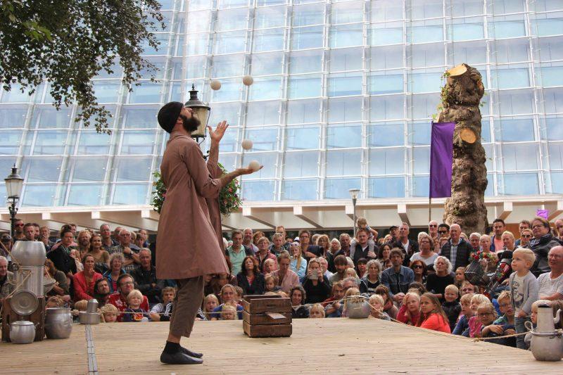 Jongleur met ballen op een podium met publiek er omheen
