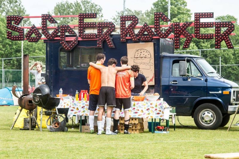 Drie voetbalvrienden staan te wachten op eten op het SoccerRocker festivalterrein
