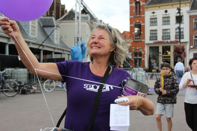 Een foto van een lachende vrouw die op een plein staat met een t-shirt van het Spoffin festival. Ze kijkt omhoog naar een van de paarse ballonen die ze in haar hand heeft. Op de achtergrond zie je een jongetje en een vrouw naderen.