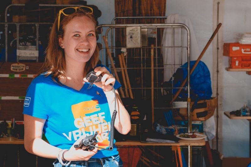 Een lachende jongedame met een helblauw t-shirt aan van het brvrijdingsfestival met een protofoon in haar handen. De portofoon lijkt ze te gebruiken. Op de achtergrond zie je de backstage van het bevrijdingsfestival