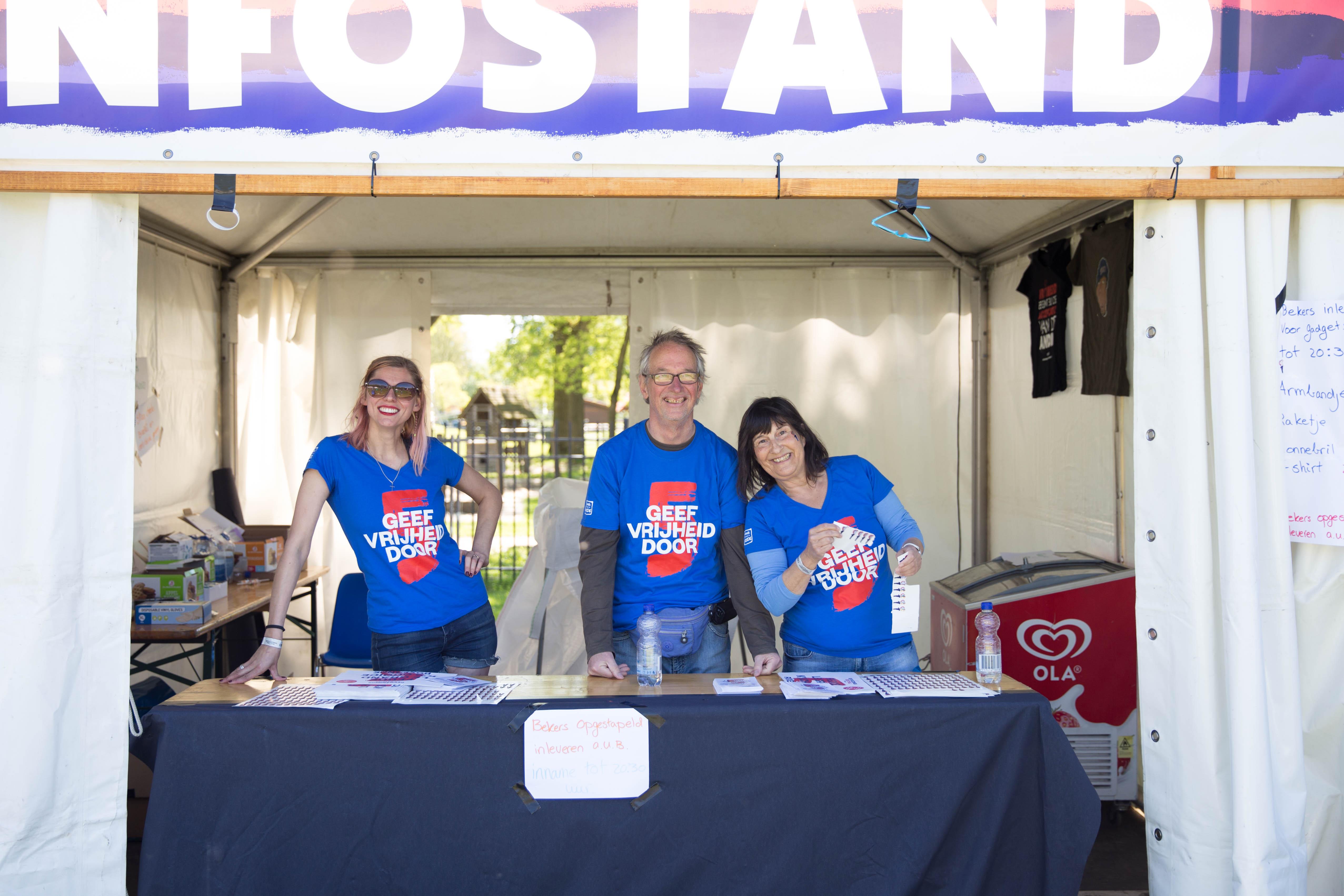 Een zonnige foto van een infostand waarin drie mensen staan achter een tafel,. Zij dragen alle drie het helblauwe t-shirt van het bevrijdingsfestival.
