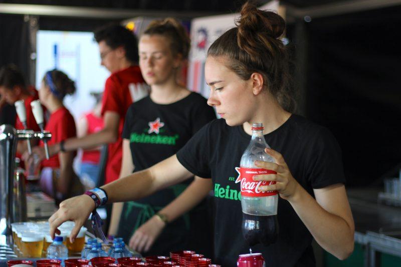 KEES vrijwilliger bij WOO HAH! die cola inschenkt
