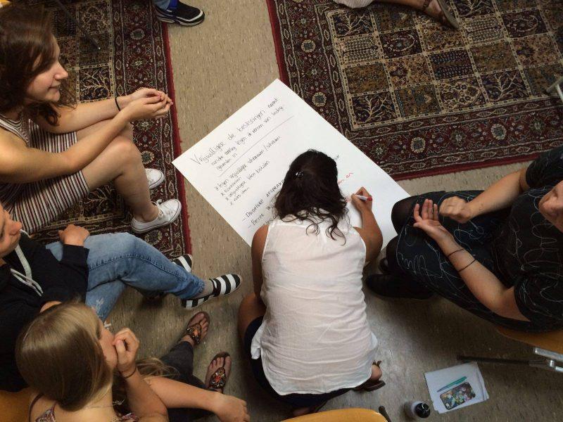 Deelnemers tijdens de KEES-training coördinatoren schrijven op A5 papier een opdracht uit