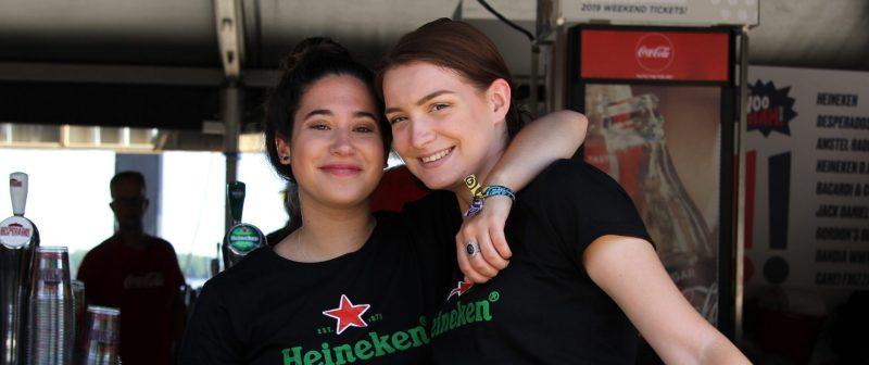 twee meisjes staan naast elkaar, het ene meisje heeft haar arm geslagen over de schouder van het andere meisje. De meisjes dragen beide een zwart T-shirt met een logo van Heineken erop. Ze lachen en geven de indruk plezier te hebben samen. De achtergrond is een bar, de meisjes lijkendaardoor werkzaam achter de bar.