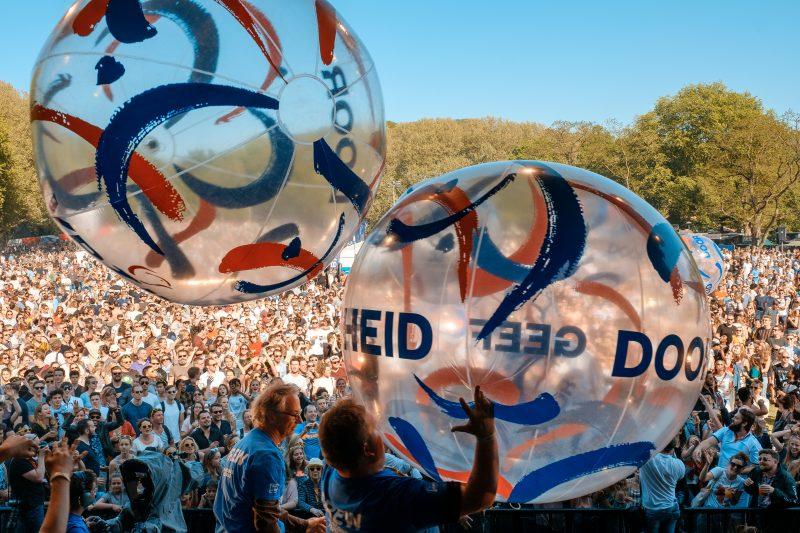 Verschillende meer dan manshoge plastic opblaasballen worden vanaf een podium over de hoofden van het festivalpubliek doorgegeven. Bevrijdingsfestival Utrecht