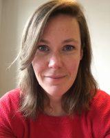 Profielfoto van KEES-trainer Eva Zwaving van de Stichting Kees Cultuurvcrijwilligers. Het is een foto van een vrouw met half lang bruin haar met een scheiding in het haar aan de linkerkant. Ze heeft blauwe ogen en ze kijkt recht de camera in. Ze draagt een roze trui met een ronde hals. Haar mond toen een lichte glimlach en is gesloten. Links op haar kaaklijn is een kleine uitstulping van de huid zichtbaar. Op haar voorhoofd, neus en onder haar ogen zijn sproeten te zien.