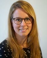Een profiel foto van Anne Elberse, projectleider bij Stichting KEES voor het project KEES Bouwt. Het is een jonge vrouw met blond lang haar. Zij heeft een scheiding in haar haar aan de rechter kant. Het haar valt deels over haar voorhoofd. Ze draagt een bril met een hoorn patroon. Ze is gekleed in een blauw shirt met witte sterretjes.