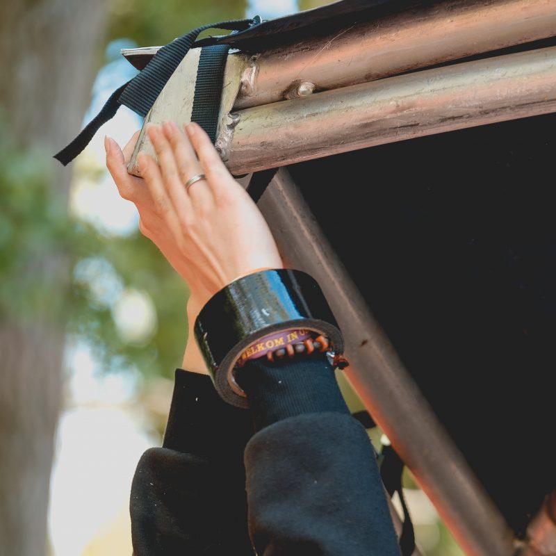 Een foto van twee vrouwen handen die constructie van steigerbuizen en zeildoek bij een hoek vasthouden. Het lijkt boven haar hoofd de onderarmen zijn gestrekt naar boven. Ze draagt arechts een ring aan haar ringvinger en een zwarte rol ducktape en een kralen armbandje om haar pols. Ze heeft lange mouwen van een zwarte sweater of hoodie.