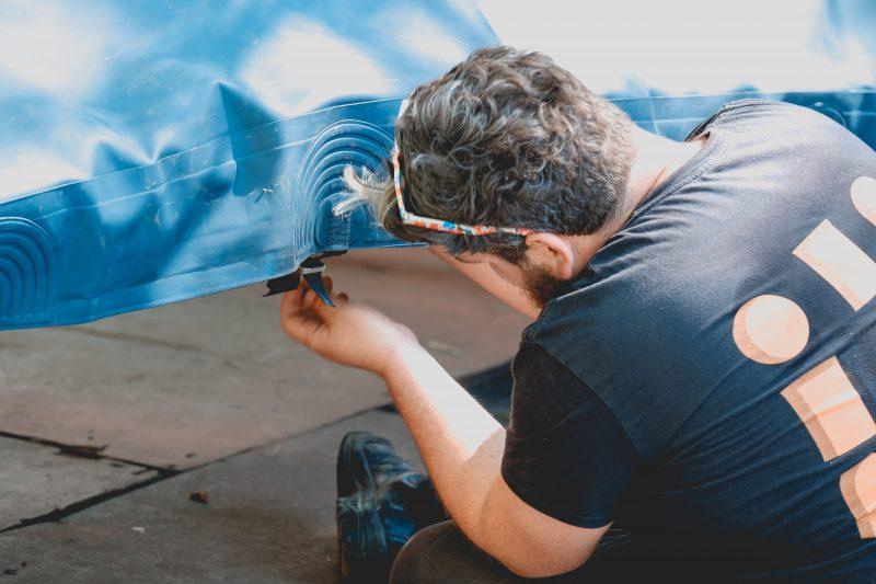 Een man met een donker t-shirt met korte mouwen en krullen haar zit voorovergebogen op de grond. we zien hem op de rug. Hij tilt een blauw zeil op en zit met zijn hand aan een bevestigingspunt. Hij draagt een bril in zijn haar met fantasiekleurige poten in oranje en blauw en wit.