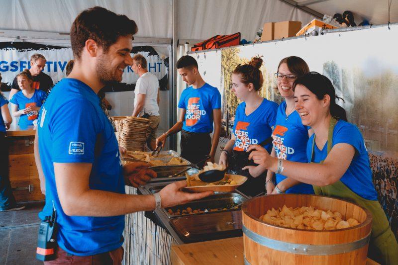 een bevrijdingsfestival eettent waar je vier vrijwilligers ziet achter een buffet vanwaaruit ze het etn opscheppen. Een man houdt zijn bord op dat wordt opgeschept. De vrijwilligers dragen allemaal een helblauw t-shirt met de tekst geef vrijheid door. Achter de tekst staat het cijfer 5 in oranje