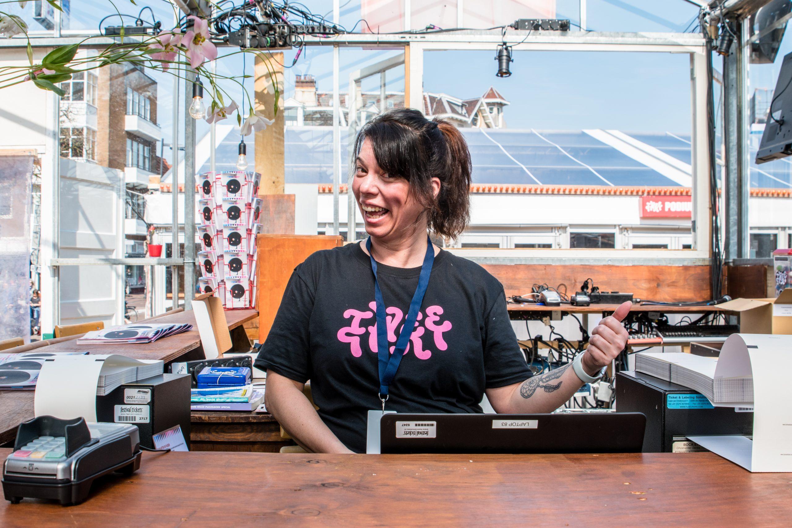 Een super blije Tweetaktvrijwilliger tijdens haar dienst achter de kassa. Ze poseert lachend voor de camera en steekt haar duim op.