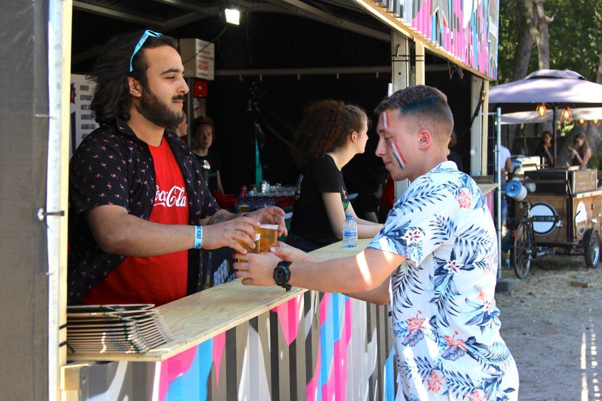 KEES bar vrijwilliger bij WOO HAH hiphopfestival die een biertje geeft aan een bezoeker