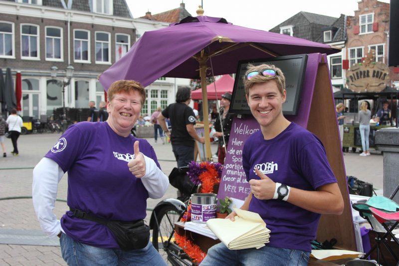 Twee vrolijke KEES Spoffin vrijwilligers in paarse T-shirts met duimen in de lucht