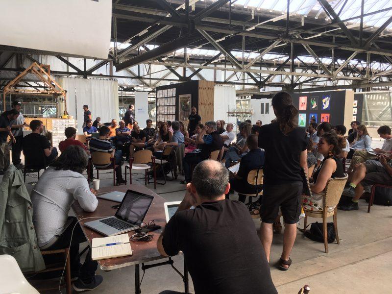 NDSM Fuse groep mensen aanwezig in grote kunstloods luisterend naar een presentatie