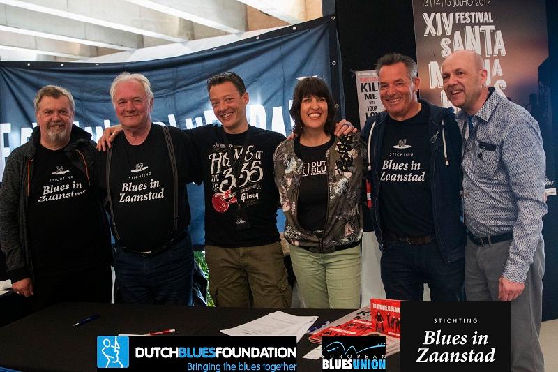 Stichting Blues-in-Zaanstad tijdens de European Blues Challenge. Hier zes personen te zien die EBC mede mogelijk hebben gemaakt dankzij hun werkzaamheden. Ze hebben een zwart T-shirt met de tekst Blues in Zaanstad aan. Onderaan de foto staan logo's van samenwerkingspartners te zien, zoals Dutch Blues Foundation, European Blues Union en Stichting Blues in Zaanstad.