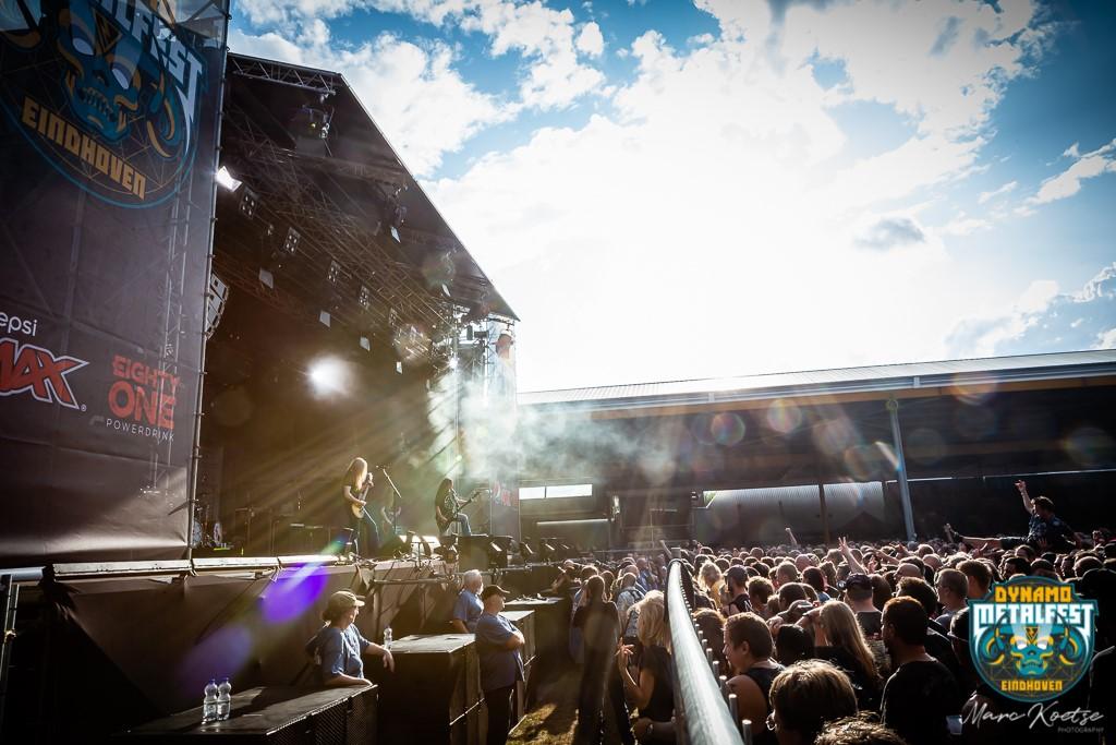 Sfeerbeeld van Dynamo Metal Fest waarop een groot podium, juichend publiek en een metalband te zien zijn.